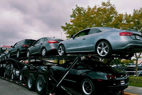 Open transport truck delivering luxury cars