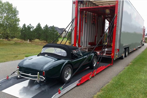 Classic car being loaded into an enclosed trailer