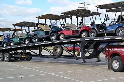 Golf Carts loaded on an open transport trailer
