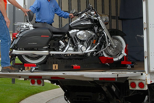 Motorcycle being loaded into an enclosed trailer