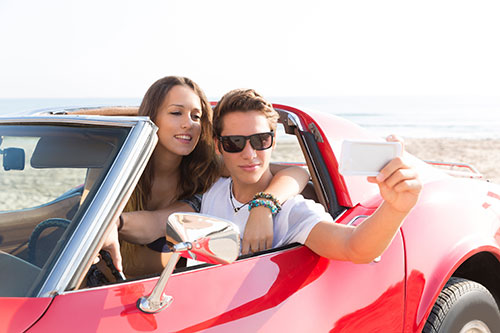 taking a selfie in a convertible on the beach